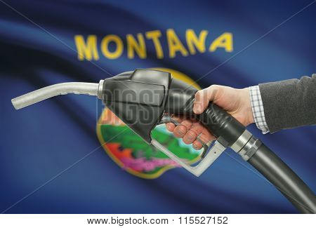 Fuel Pump Nozzle In Hand With Usa States Flags On Background - Montana