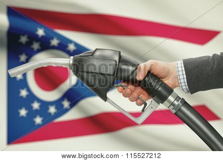 Fuel Pump Nozzle In Hand With Usa States Flags On Background - Ohio