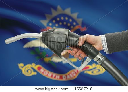 Fuel Pump Nozzle In Hand With Usa States Flags On Background - North Dakota