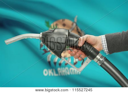 Fuel Pump Nozzle In Hand With Usa States Flags On Background - Oklahoma