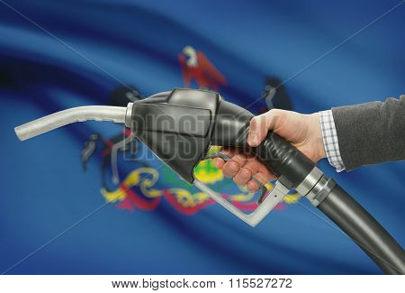 Fuel Pump Nozzle In Hand With Usa States Flags On Background - Pennsylvania