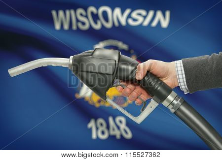 Fuel Pump Nozzle In Hand With Usa States Flags On Background - Wisconsin