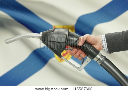 Fuel Pump Nozzle In Hand With Canadian Provinces Flags On Background - Nova Scotia