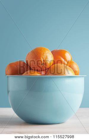 Mixed Fresh Fruits In Big Bowl In Front Of Blue Wall