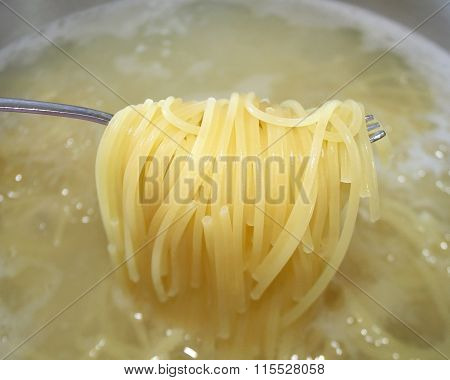 Cooked pasta noodles being lifted out of pot of boiling water with fork