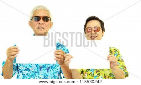 Happy Asian Senior Couple Holding White Blank Sign Ready For Holiday Trip