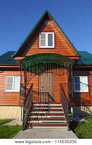 Wooden House With Green Metal Roof Front Steps View