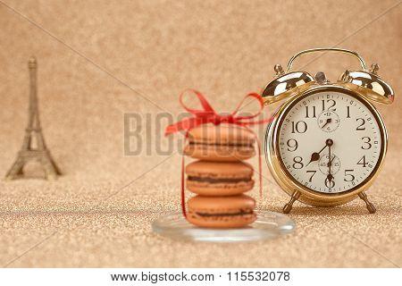 Macarons. Gold stylish alarm clock, Eiffel Tower