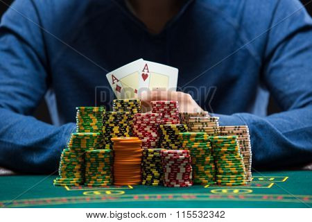 Poker player showing a pair of aces. Closeup