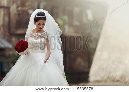 Elegant Emotional Brunette Bride In Stylish White Dress With A Rose Bouquet Walking In Old Lviv Stre