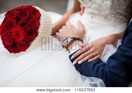Closeup Of Bride In A Elegant White Dress And With A Rose Bouquet Holding Groom's Stylish Hand With