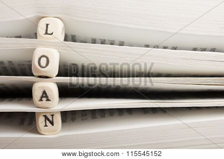 Wooden Blocks with text Loan and book pages