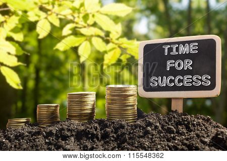 Time for success - Financial opportunity concept. Golden coins in soil Chalkboard on blurred natural
