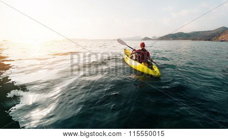 Lady paddling the sea kayak far away from the shore