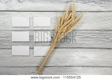 Wheat Ears on Wooden Table with blank business cards. Harvest concept.