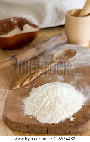 flour and a wooden spoon on a chopping board