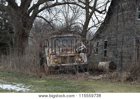 a old forgotten truck along a abandoned building