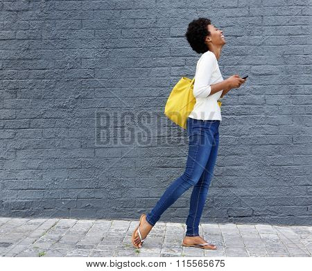 Smiling Black Woman Walking On Street With Cell Phone