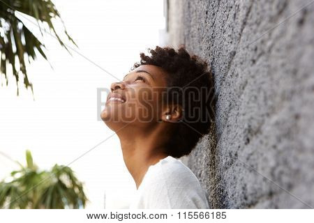 Young African Woman Leaning To A Wall Outside And Looking Up