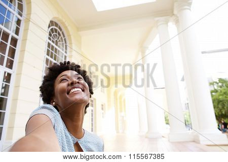Smiling Young Woman Sitting Outdoors Taking Selfie