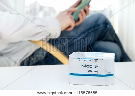 Mobile WiFi router device on the table and businessman