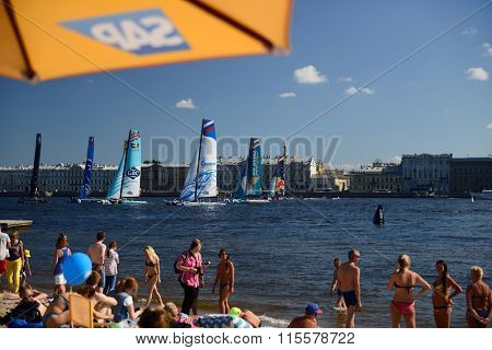 ST. PETERSBURG, RUSSIA - AUGUST 23, 2015: People on the beach watching races of Extreme 40 catamarans during St. Petersburg stage of Extreme Sailing Series. The Wave, Muscat team leading after 3 days