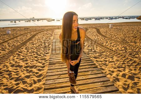 Woman taking off her shoes on the beach
