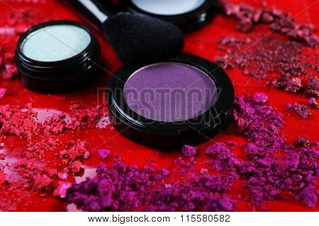Crushed pink rouges with blue and violet shadows on red background