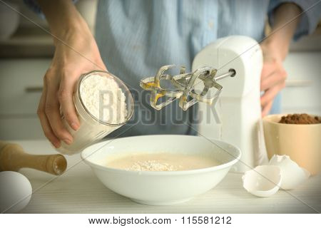 Woman is adding flour to the mixture
