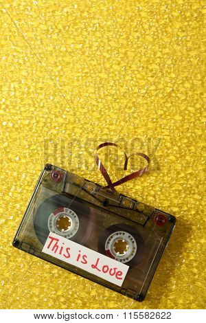 Retro audio cassette with tape in shape of heart on yellow textured background