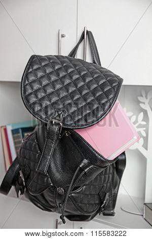 Fashion female backpack hanging on bookcase
