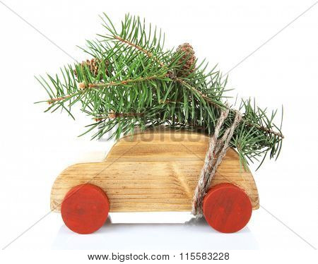 Wooden toy car with fir sprigs, isolated on white