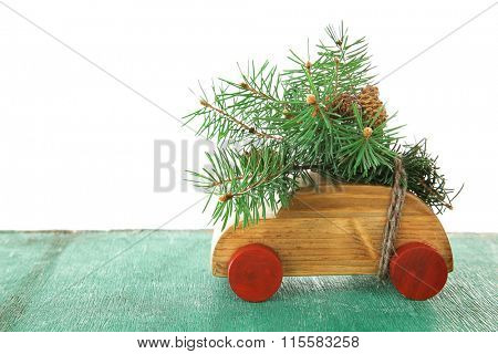 Wooden toy car with fir sprigs on a table over white background