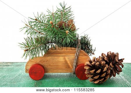 Wooden toy car with fir sprigs and cones on a table over white background