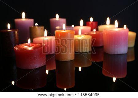 Many burning small candles on dark background