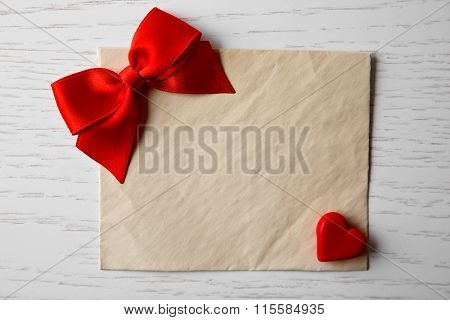 Blank present card with heart and ribbon bow on wooden background