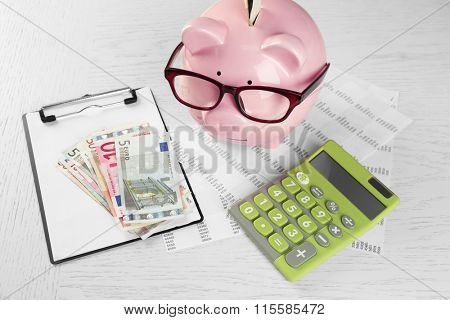Bookkeeping concept. Piggy bank, calculator, euro and papers on white wooden background