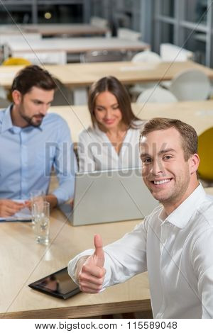 Cheerful young colleagues are discussing their job