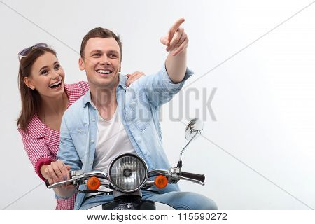 Cheerful young loving couple is driving motorbike