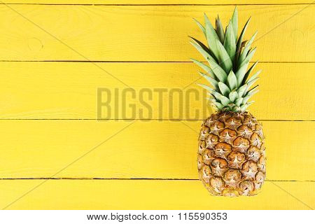 poster of Ripe Pineapple On A Yellow Wooden Background