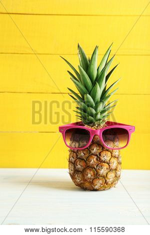 Ripe Pineapple With Sunglasses On A White Wooden Table
