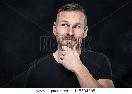 Young man thinking about something pleasant.