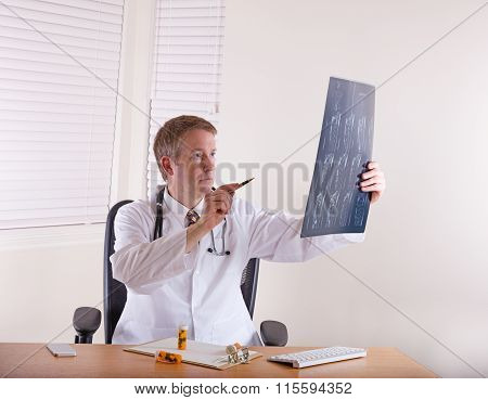 Doctor Pointing Pen At X-ray Chart
