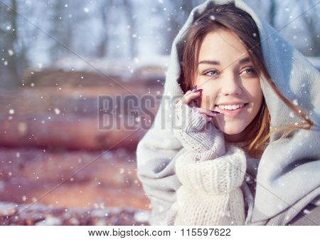 Beautiful smiling happy young woman covered in blanket and snow flakes sitting on pile of pine logs. Snowing winter outdoor leisure concept.