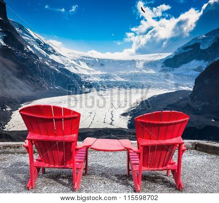 Two red plastic chairs, interconnected, facing the famous glacier Columbia
