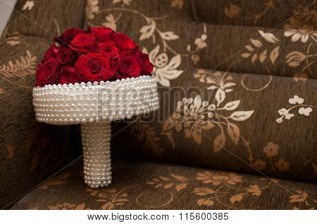Elegant Wedding Bouquet With White Pearls And Red Romantic Roses On A Couch Closeup