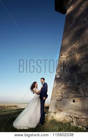 Romantic Fairytale Couple Of Newlyweds Posing At Sunset Near Old Baroque Castle Wall