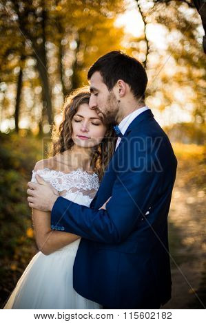 Fairytale Romantic Valentyne Newlywed Couple Hugging And Posing Under Old Castle Bridge At Sunset In