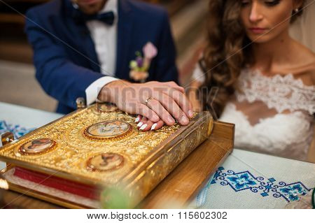 Bride And Groom Taking Vows In Church On Old Golden Bible Hands Closeup