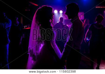 Romantic Couple Of Newlyweds Silhouettes Posing At Wedding Reception Surrounded By Purple Lights